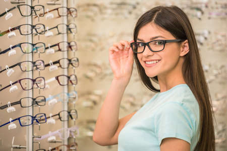 Young woman is choosing a glasses in optician store.