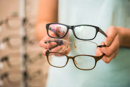 vision repair: Close-up of young woman hands is holding glasses to choosing.