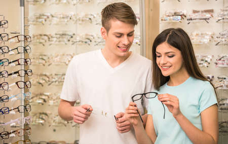 eye wear: Young couple at optician in the store, they looking for glasses.