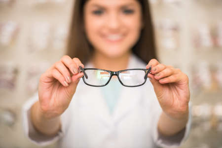 Optometrist is looking at the camera in glasses store. Professional young worker woman.