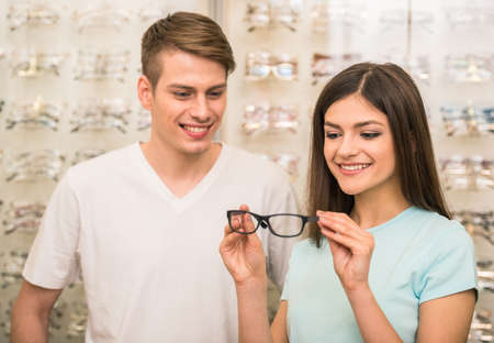Young couple at optician in the store, they looking for glasses. photo