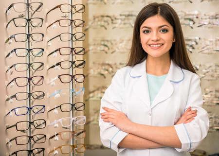 Optometrista está mirando a la cámara en las gafas tienda. Mujer joven trabajador profesional.
