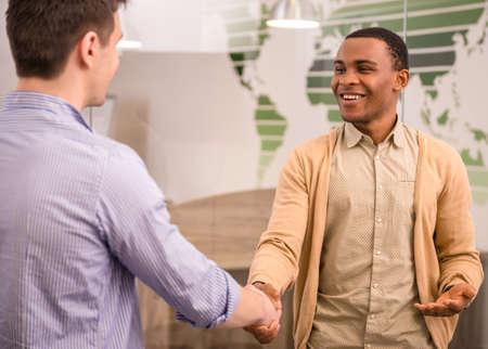 apreton de manos: Hombre de negocios sonriente apretón de manos con su colega. Vista trasera. Foto de archivo