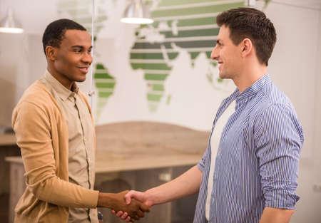 manos estrechadas: Los apretones de manos de dos hombres de negocios internacionales en ropa casual.