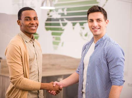 poign�es de main: Poign�es de mains de deux hommes d'affaires internationaux dans des v�tements d�contract�s.