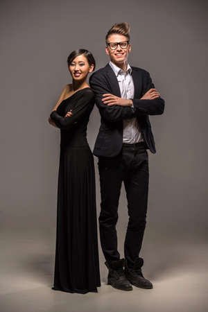 formal clothing: Full length photo of young  smiling couple dressed in formal clothing posing in the studio on dark background. Stock Photo