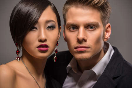 formal clothing: Young fashionable couple dressed in formal clothing posing in the studio on dark background. Fashion portrait.