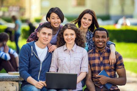 estudiantes universitarios: Grupo de jóvenes estudiantes sonrientes atractivos vestida sentada ocasional en la escalera al aire libre en el campus de la universidad. Foto de archivo