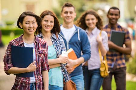젊은 매력적인 미소 학생들의 그룹 공원에서 함께 공부하는 캐주얼 옷을 입고.