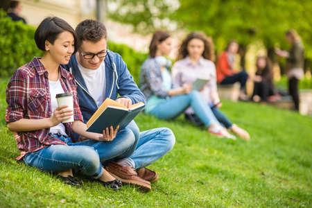 매력적인 미소 학생들의 커플은 대학 캠퍼스에 야외에서 공부 캐주얼 옷을 입고.