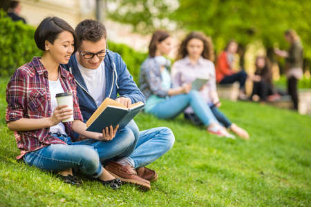 college: Couple of attractive smiling students dressed casual  studying outdoors on campus at the university.