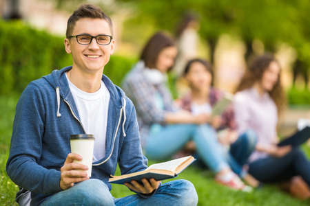 Young smiling student sitting on the lawn with cup of coffee and reading book.