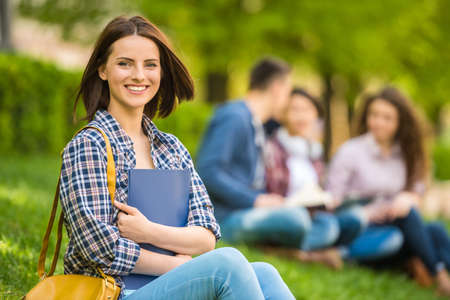 Young beautiful smiling student sitting on the lawn with friends and reading.