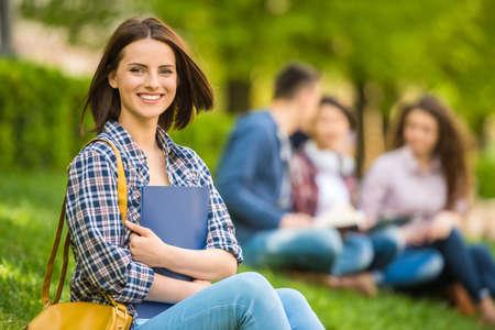 vysoká škola: Mladá krásná usmívající se student sedí na trávníku s přáteli a čtení. Reklamní fotografie