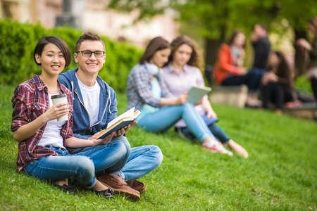 studie: Několik atraktivních usmívající se studenty, oblečený ležérní studuje venku na akademické půdě na univerzitě.