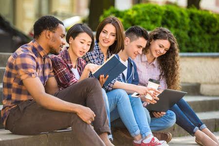 젊은 매력적인 미소 학생의 그룹 야외 대학 캠퍼스 계단에 앉아 캐주얼 옷을 입고.