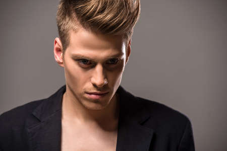 modelos hombres: Hombre hermoso joven en smoking posando en el estudio sobre fondo oscuro. Retrato de la moda.