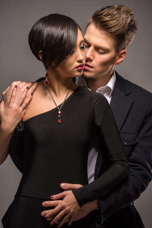 formal clothing: Young fashionable couple dressed in formal clothing posing in the studio on dark background. Fashion portrait. Passion.