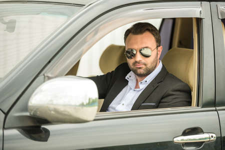 Successful mature man in formal wear sitting in classy car. photo