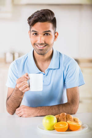 manin: Young handsome manin blue t-shirt  sitting in the kitchen and having breakfast.