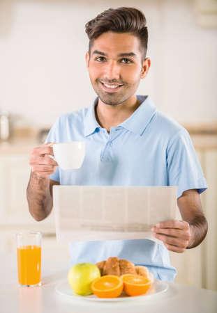 eating fruits: Apuesto hombre bebiendo caf� Joven y comer frutas para el desayuno. Foto de archivo