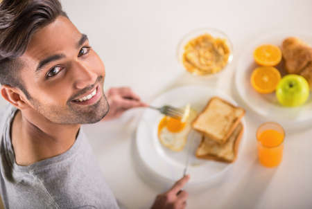 breakfast eggs: Young handsome man in grey t-shirt eating breakfast. Stock Photo