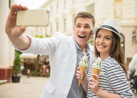romantico: Hermosa joven pareja caminando en la calle y disfrutar de un helado. Cita romantica. Foto de archivo