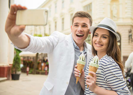 romantic picture: Young beautiful couple walking in the street and enjoying ice-cream. Romantic date.