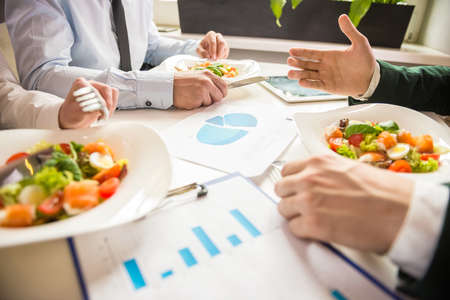 lunch meal: Close-up of business partners discussing the project during business lunch. Stock Photo