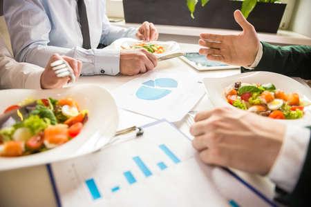 lunch: Primer plano de socios de negocios en discusiones sobre el proyecto durante el almuerzo de negocios. Foto de archivo