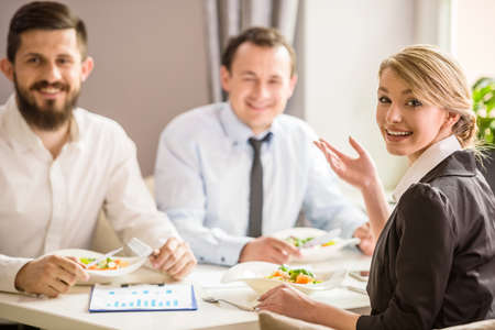 lunch: Hermosa mujer de negocios en juego que habla con los socios en el almuerzo de negocios.