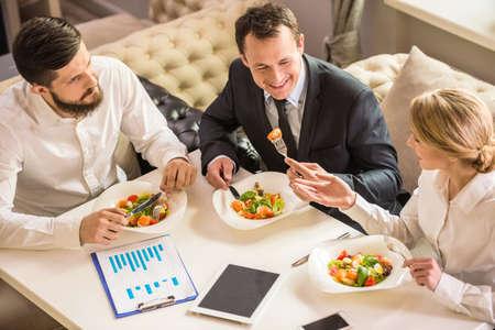 negocios comida: Hombres de negocios en ropa formal hablando de algo durante el almuerzo de negocios.