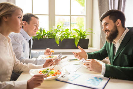 businessman talking: Group of successful business people at business lunch in cafe.