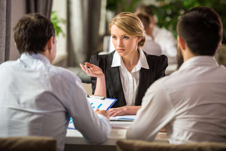 business goal: Beautiful businesswoman in suit talking with partners at business lunch. Stock Photo
