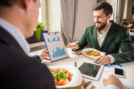 personas mirando: Dos hombres de negocios maduros mirando la carta en el almuerzo de negocios.