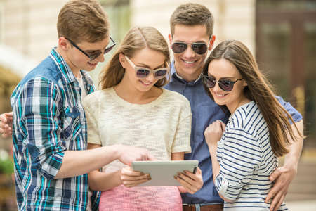 the double: Double couple date. Friends walking down the street together and using digital tablet. Stock Photo