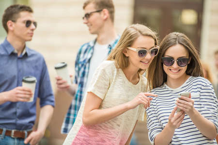 mobile devices: Double couple date. Friends walking down the street together and making selfie.