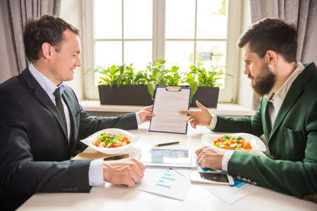 business table: Two confident businessmen discussing contract at business lunch in cafe.