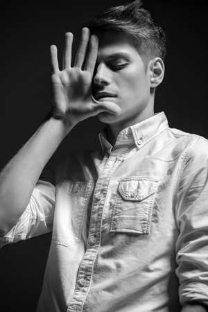 modish: Young handsome man dressed casual posing in the studio on dark background. Black and white fashion portrait.