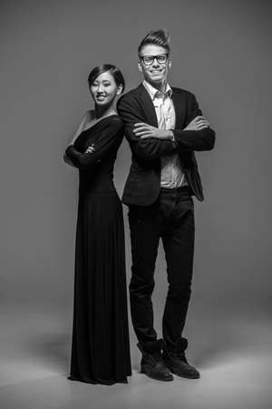 formal clothing: Full length photo of young  smiling couple dressed in formal clothing posing in the studio. Black and white fashion photo.
