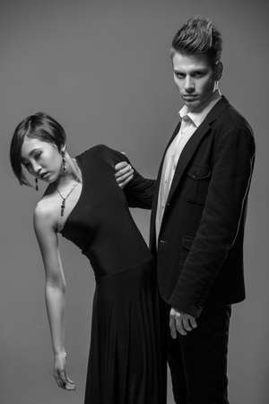 formal clothing: Young fashionable couple dressed in formal clothing posing in the studio. Black and white fashion portrait. Jealousy.