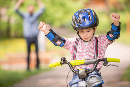 cycle ride: Young father teaching son to ride bicycle in summer park. Stock Photo