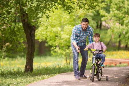 夏の公園で自転車に乗る息子を教える若い父親。