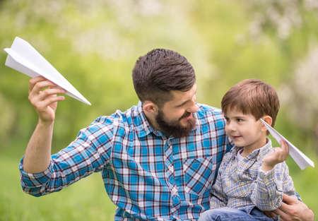 padres: Padre e hijo se divierten juntos en el parque de verano.