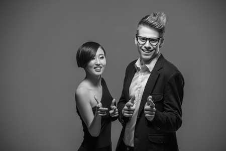 formal clothing: Young smiling couple dressed in formal clothing posing in the studio. Black and white fashion portrait. Fun.
