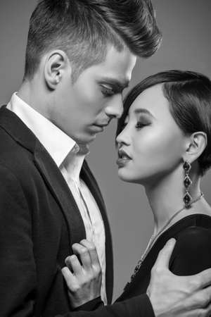 formal clothing: Young fashionable couple dressed in formal clothing posing in the studio. Black and white fashion portrait. Passion.