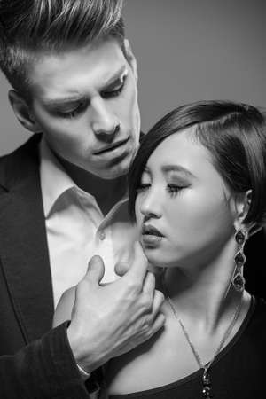 Young fashionable couple dressed in formal clothing posing in the studio. Black and white fashion portrait. Passion. photo