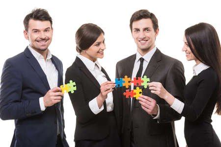 put together: Image of business people wanting to put pieces of puzzle together.