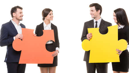 wanting: Image of four confident people wanting to put pieces of puzzle together. Team work. Stock Photo