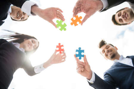Closeup of business people wanting to put four pieces of puzzle together. Team work. Reklamní fotografie
